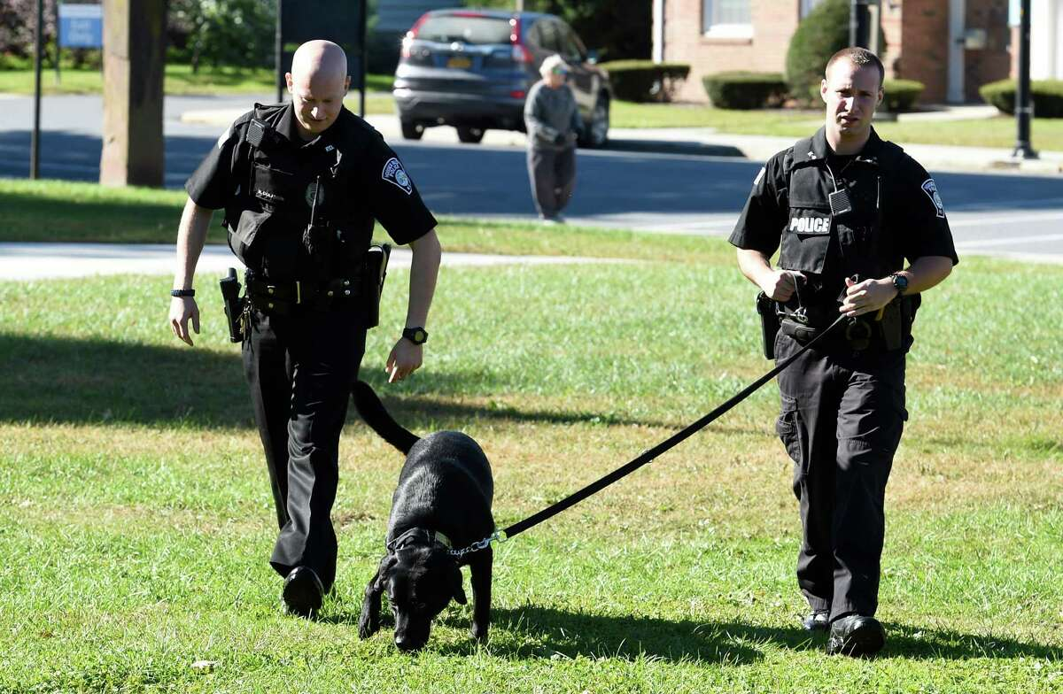 Patrolman Nick Colaneri, left, walks with partner Cory Wagner and his partner K-9 Mick near Main Street Tuesday morning, Oct. 6, 2015, in Hoosick Falls, N.Y. (Skip Dickstein/Times Union)