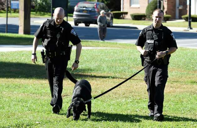 Patrolman Nick Colaneri, left, walks with partner Cory Wagner and his partner K-9 Mick near Main Street Tuesday morning, Oct. 6, 2015, in Hoosick Falls, N.Y. (Skip Dickstein/Times Union) Photo: SKIP DICKSTEIN / 10033623A