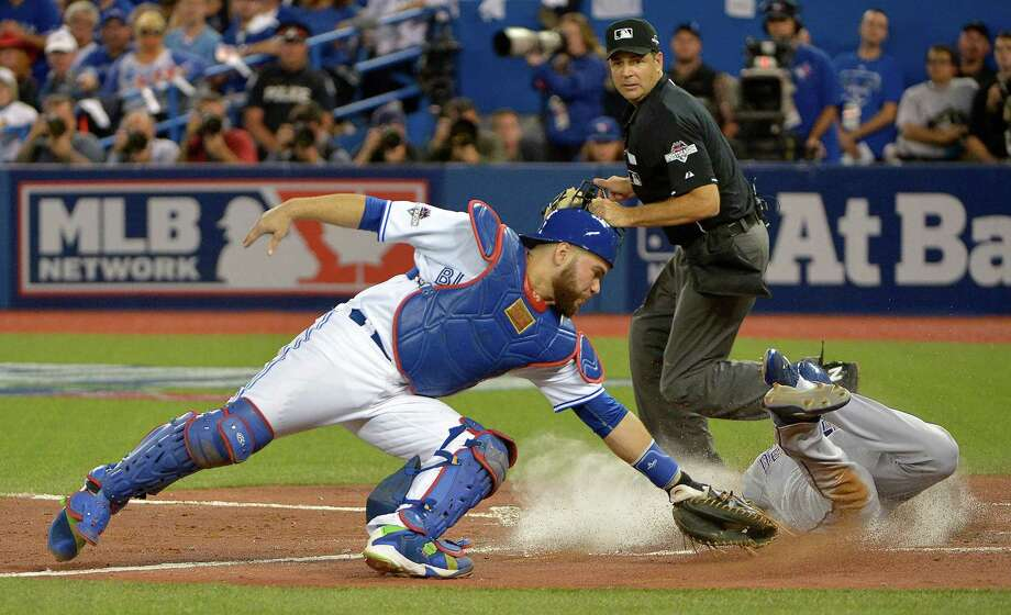 The Texas Rangers' Delino DeShields, right, scores on a single by teammate Adrian Beltre in the third inning as Toronto Blue Jays catcher Russell Martin, left, can't make the tag during Game 1 of the ALDS at Rogers Centre in Toronto on Thursday, Oct. 8, 2015. The Rangers won, 5-3. (Max Faulkner/Fort Worth Star-Telegram/TNS) Photo: Max Faulkner, McClatchy-Tribune News Service / Fort Worth Star-Telegram