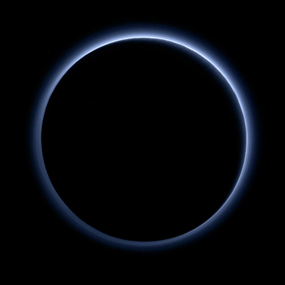 This image released by NASA on Thursday, Oct. 8, 2015, shows the blue color of Pluto's haze layer in this picture taken by the New Horizons spacecraft's Ralph/ Multispectral Visible Imaging Camera (MVIC). The high-altitude haze is thought to be similar in nature to that seen at Saturn's moon Titan. This image was generated by software that combines information from blue, red and near-infrared images to replicate the color a human eye would perceive as closely as possible. (NASA/JHUAPL/SwRI via AP Photo: / Associated Press / NASA/JHUAPL/SwRI