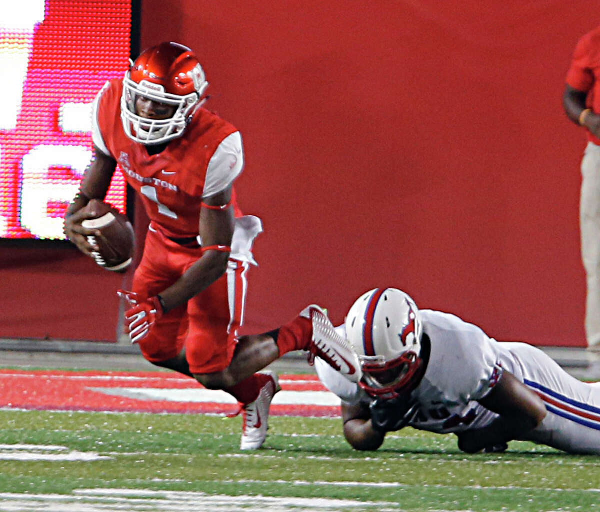 Houston Cougars quarterback Greg Ward Jr. left, is tripped up by Southern Methodist Mustangs defensive lineman Jarvis Pruitt right, during the first half of men's college football game action at TDECU Stadium Thursday, Oct. 8, 2015, in Houston.