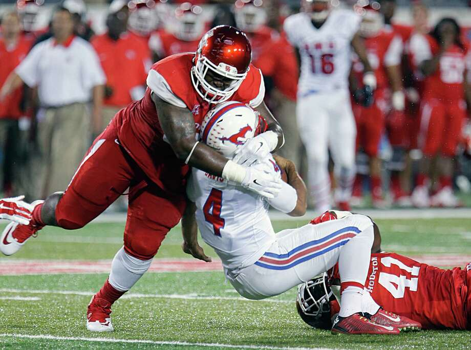 Houston Cougars defensive tackle Tomme Mark left, and Cougars linebacker Steven Taylor right, tackle Southern Methodist Mustangs quarterback Matt Davis center, during the first half of men's college football game action at TDECU Stadium Thursday, Oct. 8, 2015, in Houston. Photo: James Nielsen, Houston Chronicle / © 2015  Houston Chronicle