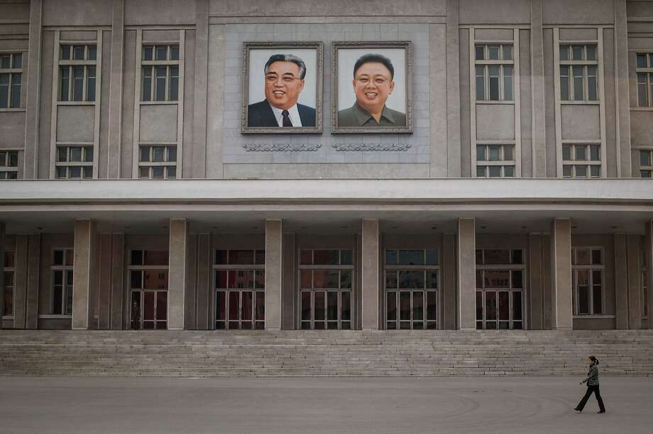 A woman, above, walks past portraits of Kim Jung Un's father and grandfather; a view,top left, shows the Pyongyang skyline; Men, bottom left, carry decorative flowers and women gather for rehearsals. Photo: Ed Jones, AFP / Getty Images