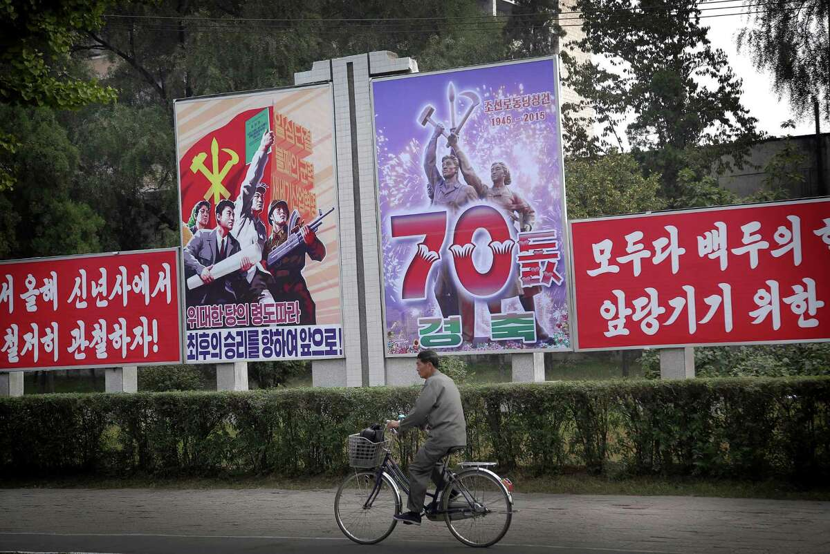 A man cycles past a signboard marking the upcoming 70th anniversary of the founding of North Korea's Workers' Party, Thursday, Oct. 8, 2015, in Pyongyang, North Korea. The country is in high gear with preparations for the anniversary on Oct. 10. 2015. (AP Photo/Wong Maye-E) ORG XMIT: XWM103
