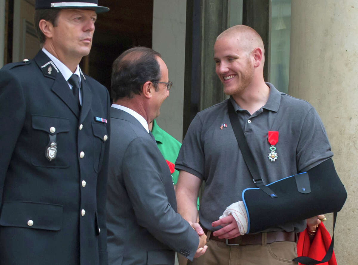 FILE - In this Aug. 24, 2015 file photo, French President Francois Hollande shakes hands with U.S. Airman Spencer Stone outside the Elysee Palace in Paris after Hollande awarded Stone and two friends with the French Legion of Honor for subduing a gunman on a Paris-bound train three days earlier. Stone is in stable condition Thursday, Oct. 8, 2015, after being stabbed in Sacramento, Calif., according to an Air Force spokesman. (AP Photo/Kamil Zihnioglu, File) ORG XMIT: NY112