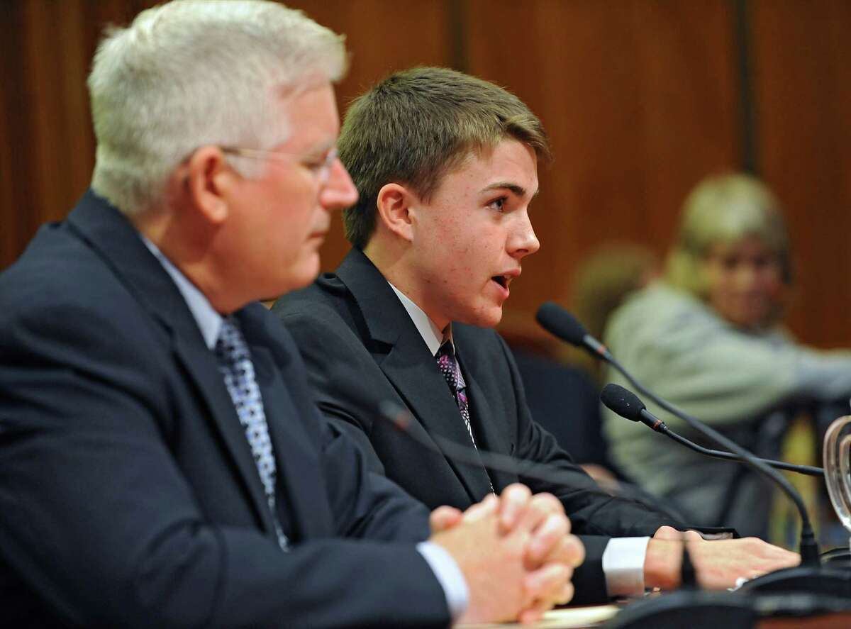 Joseph Fischer, right, a student at City Honors School in Buffalo, talks about incurring a serious concussion while playing football during a hearing on services and medical care for those with traumatic brain injury on Thursday, Oct. 8, 2015 at the Legislative Office Building in Albany, N.Y. Assembly member Michael Kearns sits next to him. His hometown news did a segment about him. http://www.wkbw.com/news/local-teen-to-testify-at-brain-injury-hearing (Lori Van Buren / Times Union)