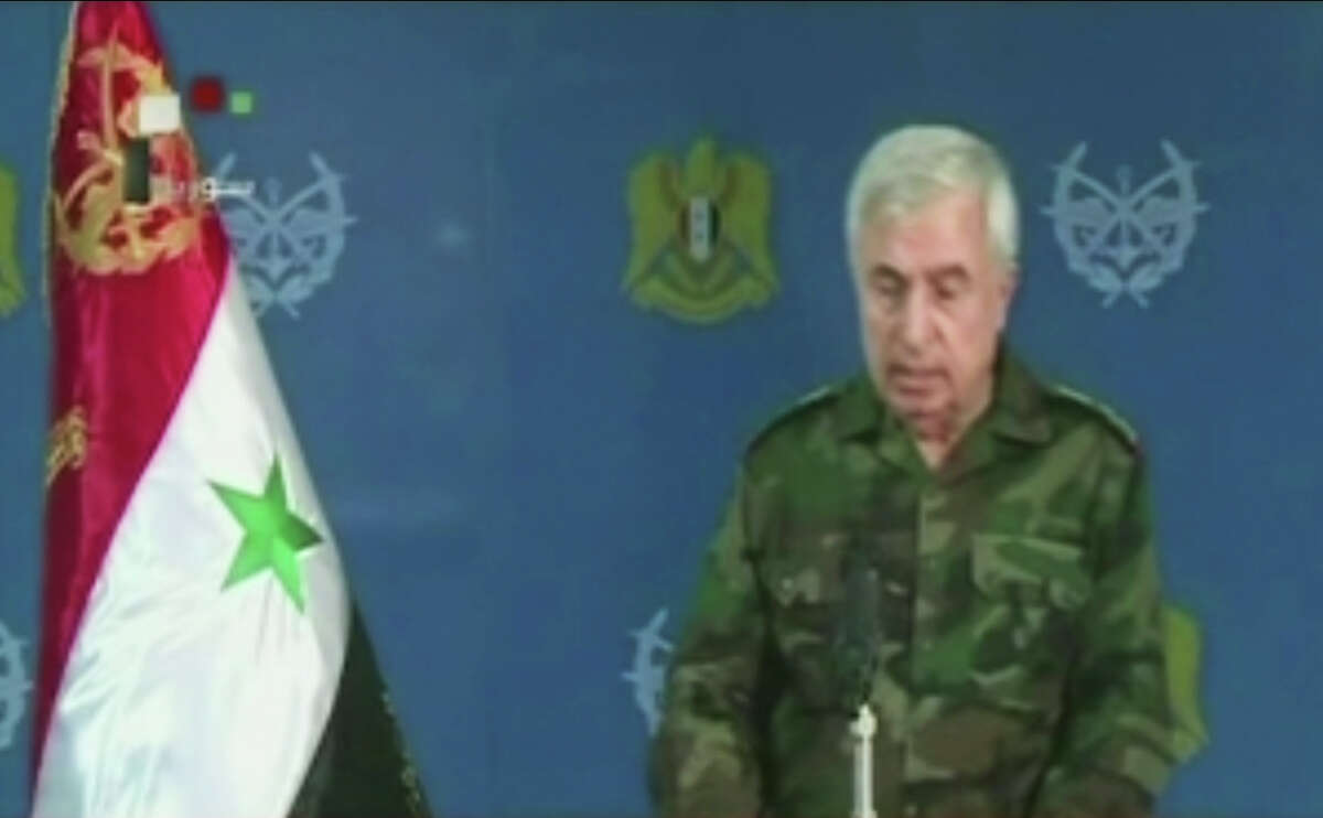 In this frame grab from video provided taken from Syrian TV via Al Manar, Gen. Ali Ayoub, Syria's chief of staff, speaks, Thursday, Oct. 8, 2015, in Damascus, Syria. Ayoub said in a rare televised statement that the Russian strikes on Syria have facilitated an expanded military operation to eliminate ?