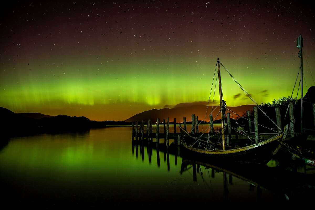 The aurora borealis, or the northern lights occur over Derwentwater, near Keswick, England, Thursday Oct. 8, 2015. The northern lights are the result of collisions between gaseous particles in the Earth's atmosphere with charged particles released from the sun. (Owen Humphreys/PA via AP) UNITED KINGDOM OUT NO SALES NO ARCHIVE