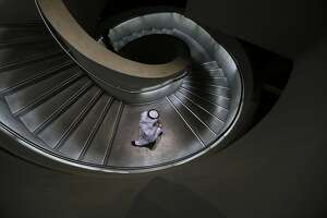TOPSHOTS An Emirati man walks down stairs in Masdar City, on the outskirts of the rich Emirate of Abu Dhabi, on October 7, 2015. Masdar City is a high-density, pedestrian-friendly development where current and future renewable energy and clean technologies are showcased, marketed, researched, developed, tested and implemented. AFP PHOTO / KARIM SAHIB .KARIM SAHIB/AFP/Getty Images