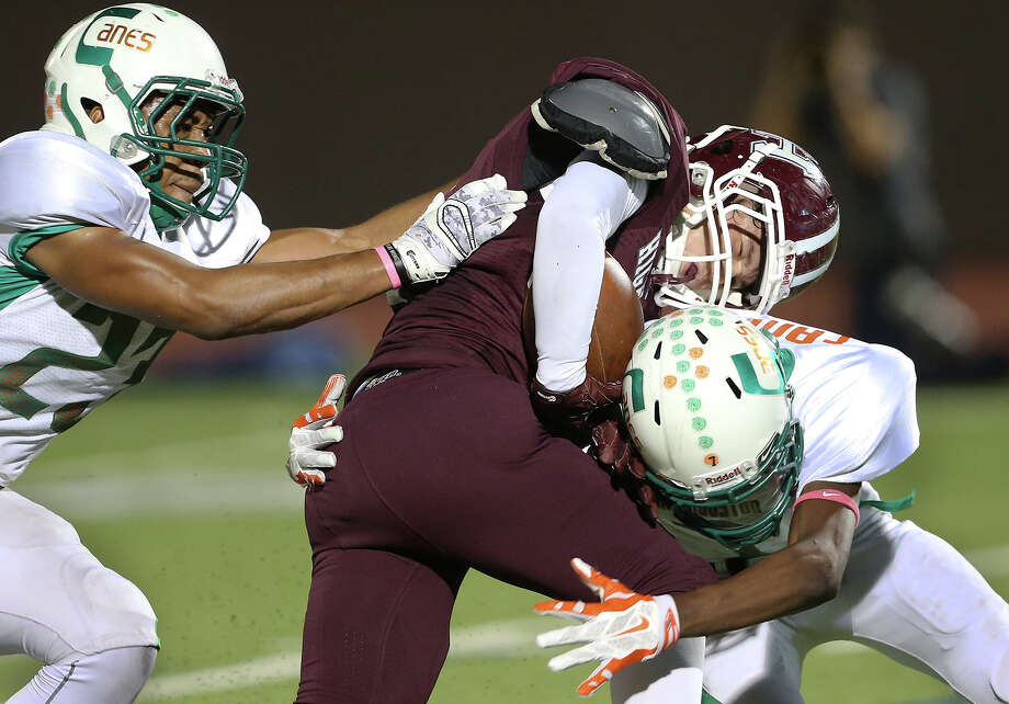 Owls fullback Julian Guerrero is smacked down hard after a long run by Deondrik Thomas (right) with teammate Jacobi Watkins helping as Sam Houston plays Highlands at Alamo Stadium on Oct. 8, 2015. Photo: Tom Reel /San Antonio Express-News / San Antonio Express-News