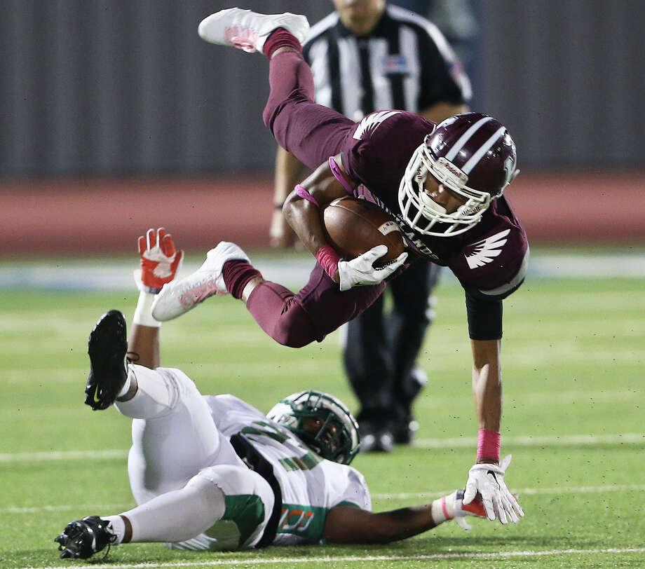 Owlsreceiver Bruce Moody goes airborne to get past Hurricane linebacker Josh Harris as Sam Houston plays Highlands at Alamo Stadium on October 8, 2015. Photo: Tom Reel / San Antonio Express-News
