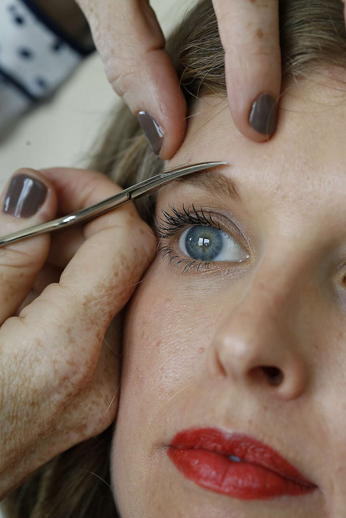 Eyebrow guru Michele McConnell uses Afore oil to condition hair before shaping the brows of Dalila Acuna in San Francisco, Calif., on Wednesday, October 7, 2015.