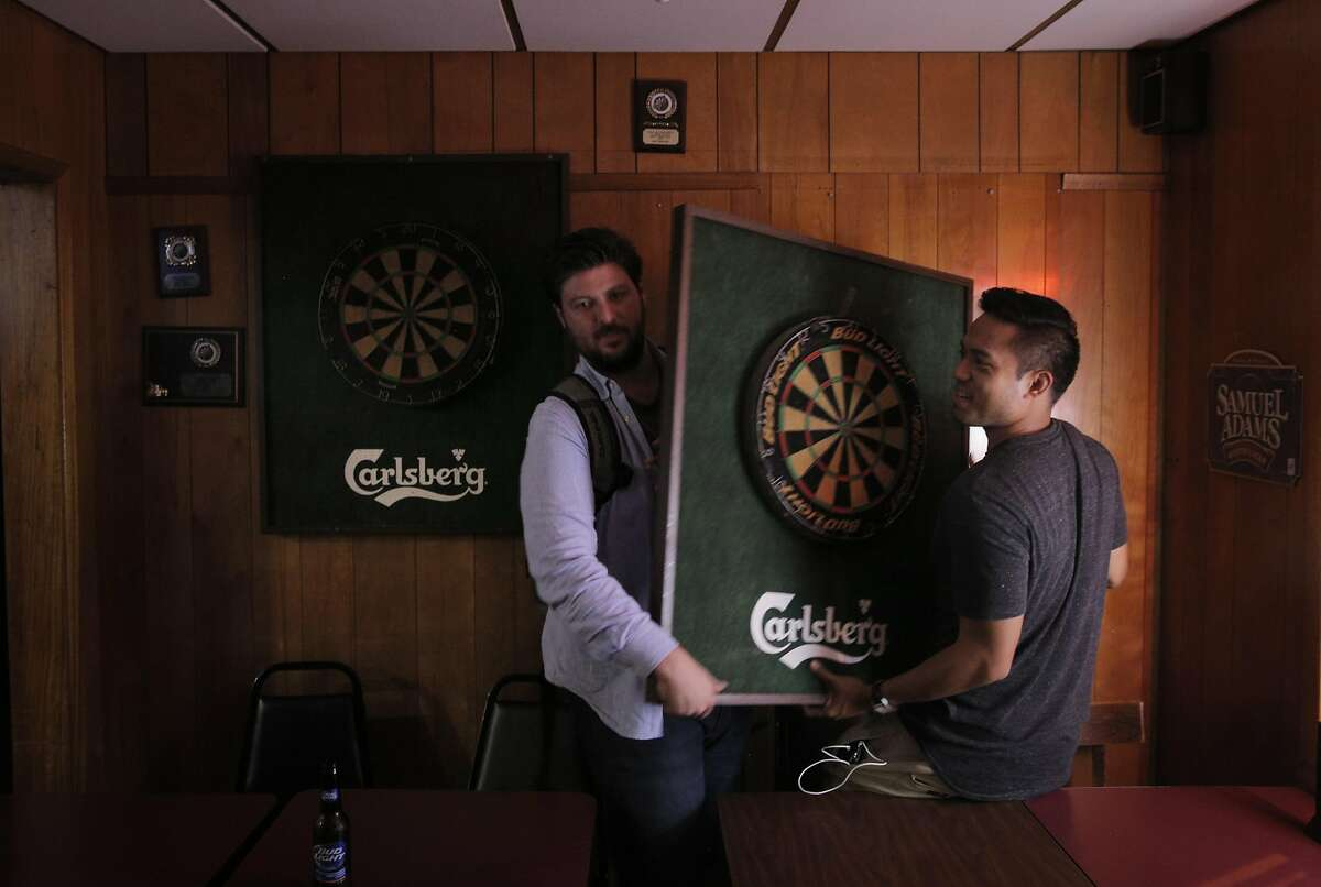 Court Toomey, left, and Joseph Millares, right, move a dart board they bought as a souvenir at Zeke's Sports Bar & Grill in San Francisco, Calif., on Thursday, October 8, 2015. Zeke's is closing on Saturday after serving decades of sports fans near AT&T Park.