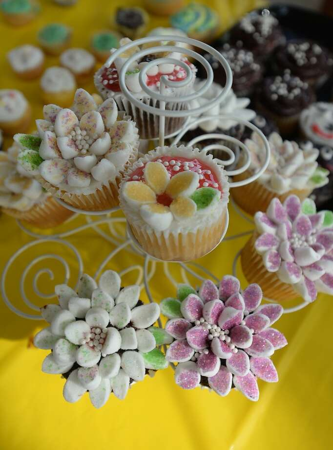 A display of hand-decorated cupcakes made by young entrepreneurs are available at the Beaumont Farmer's Market Saturday morning. As the growing season hits its peak for many fruits and vegetables, the crowd at the weekly market is hitting a peak of its own. Photo taken Saturday, May 30, 2015 Kim Brent/The Enterprise Photo: Kim Brent/The Enterprise
