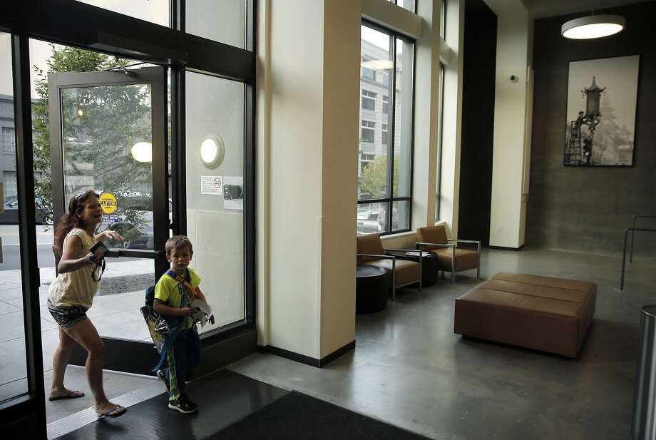 Christine Coggins and her son Caden enter the Chinatown Community Development Center in San Francisco, Calif., on Thursday, October 8, 2015. The CCDC was built on surplus city property and Proposition K on the November ballot would make city departments to come up with a list of unused property and allocate it for housing needs. Photo: Carlos Avila Gonzalez, The Chronicle