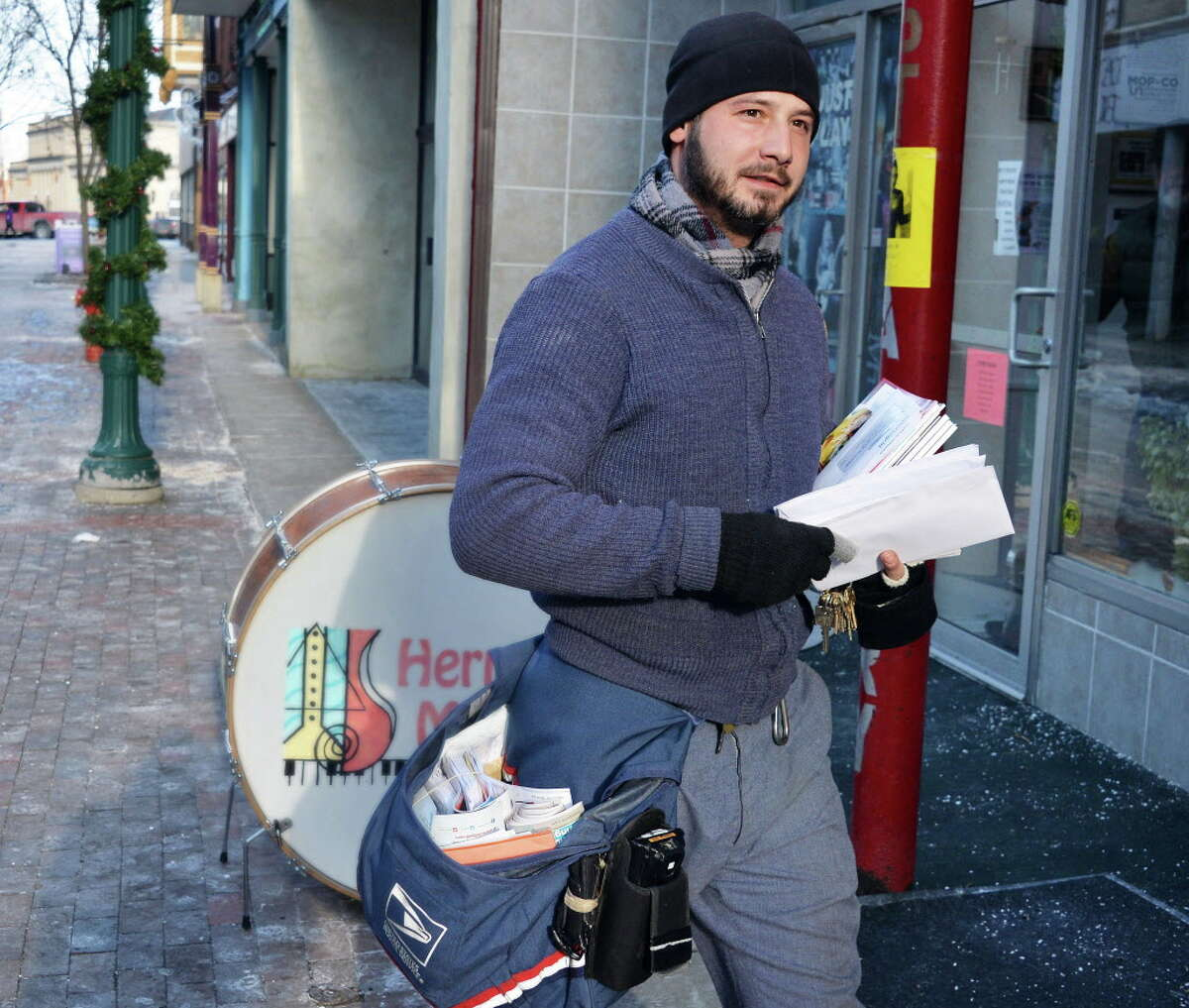 Postal carrier Andrew Mokey of Watervliet delivers mail along Jay Street Thursday Jan. 8, 2015, in Schenectady, NY.