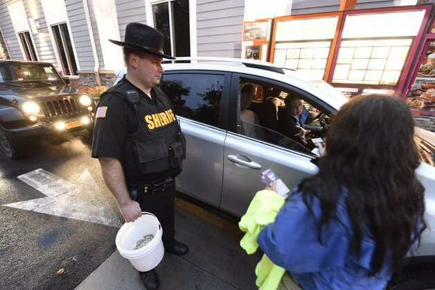 Saratoga County Sheriff's Deputy Steve Willetts assists Peg Adams of Special Olympics in a fundraiser called Cops on Top at Dunkin' Donuts in Malta, NY, on Oct. 9, 2015. (Skip Dickstein/Times Union)