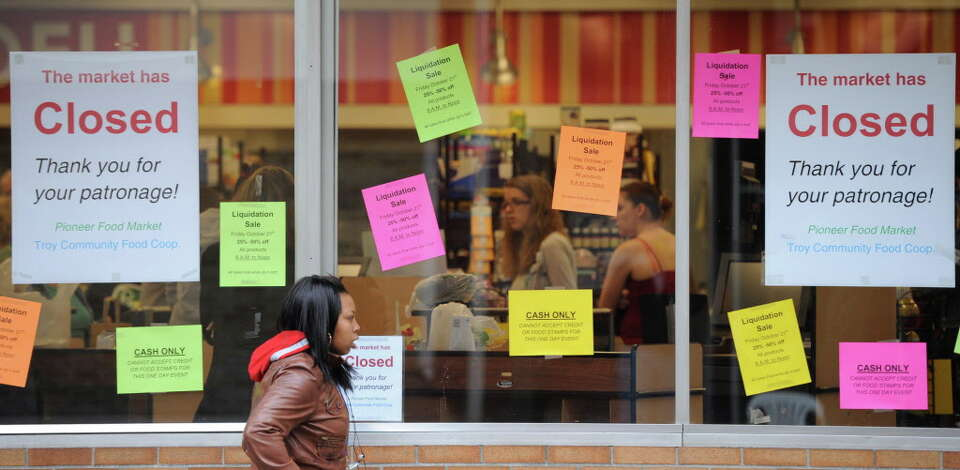 The signs on the windows of the Pioneer Food Coop in Troy, N.Y. October 21, 2011 herald the last day