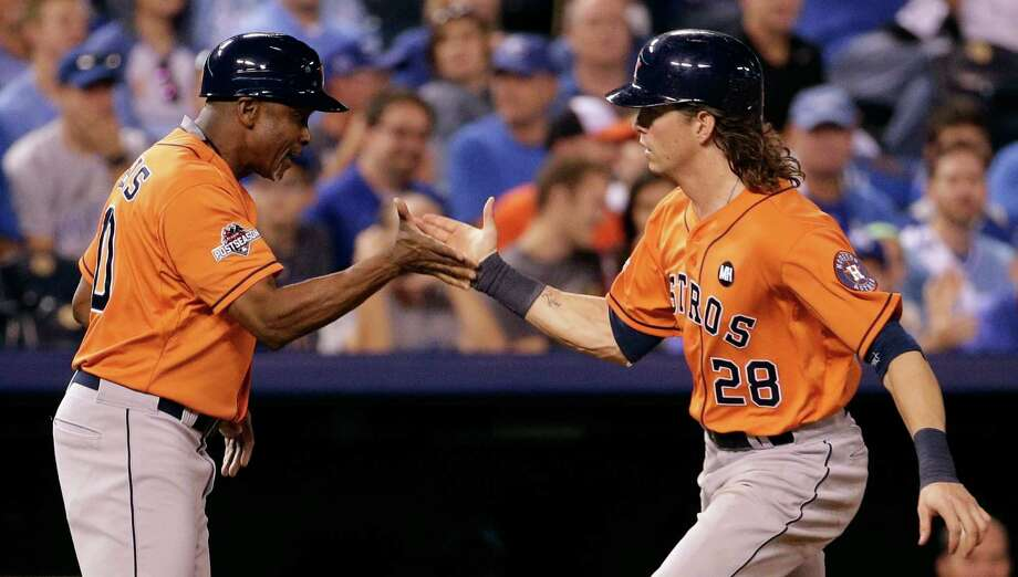 Colby Rasmus is congratulated by third-base coach Gary Pettis after a solo homer in the eighth inning gave the Astros a three-run lead they wouldn't relinquish. Game 2 is this afternoon. Photo: Charlie Riedel / Associated Press / AP