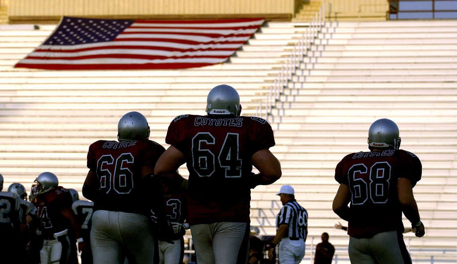 Texas Coyote football players enter the field June 15, 2002 at a virtually-empty Comalander Stadium. Fans sat on only one side of the stadium for the North American Football League franchise's home opener. Photo: William Luther /San Antonio Express-News / SAN ANTONIO EXPRESS-NEWS