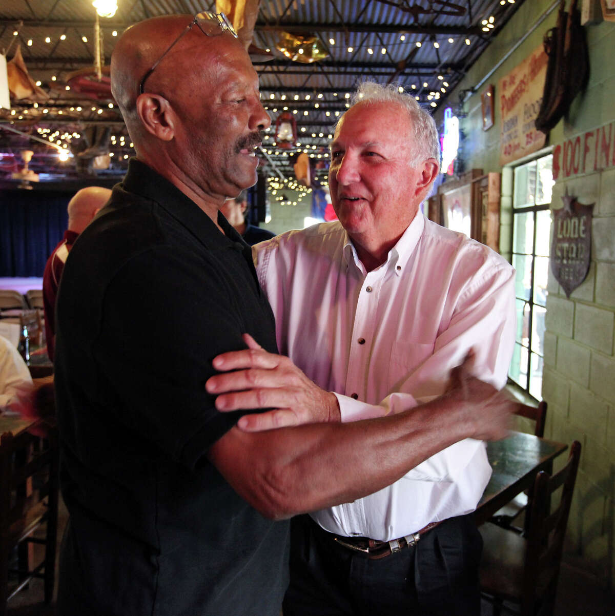 Former San Antonio Toros players Isadore Hannah (left) and Sonny Detmer joke during a reunion on April 12, 2014, at John T. Floore County Store in Helotes.