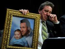 Neil Heslin, the father of Jesse, a 6-year-old boy who was killed in the Sandy Hook shooting, holds a picture of them together as he wipes his eye while testifying on Capitol Hill in Washington on the Assault Weapons Ban of 2013. The bill was defeated in the Senate.