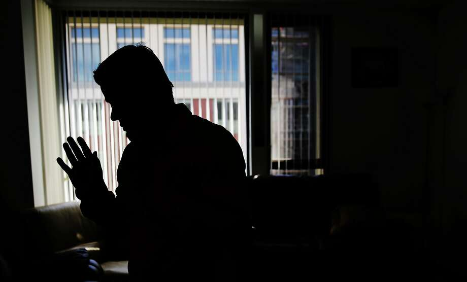 An uncle of a 15 year old who has been held in juvenile hall for nine months for what his family believes is nothing more than an administrative delay over nonviolent misdemeanor convictions stands silhouetted in his brother's home as he talks with a reporter on Thursday, October 8,  2015 in San Francisco, Calif. Photo: Lea Suzuki, The Chronicle