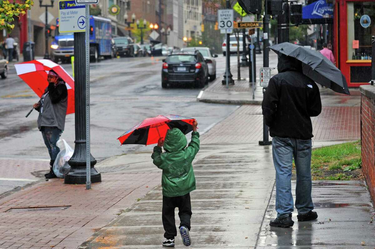 Three-year-old Ahsavion Gordon, center, walks with his father Anthony Gordon down North Pearl Street in the rain on Friday Oct. 9, 2015 in Albany , N.Y. (Michael P. Farrell/Times Union)