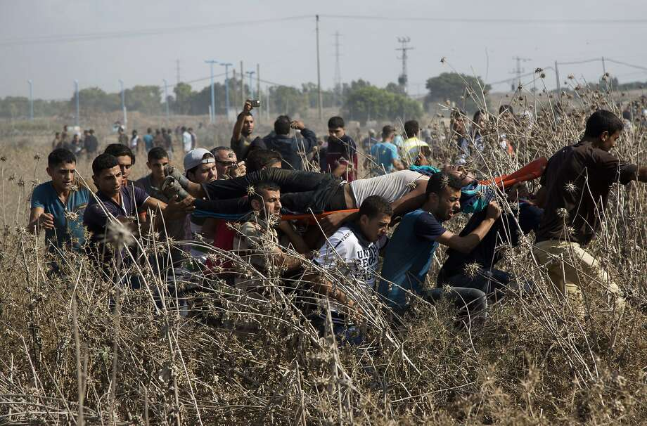 Palestinians carry a wounded youth during clashes with Israeli soldiers on the Israeli border with Gaza. Deadly clashes there have threatened to escalate tensions throughout the country. Photo: Adel Hana, Associated Press