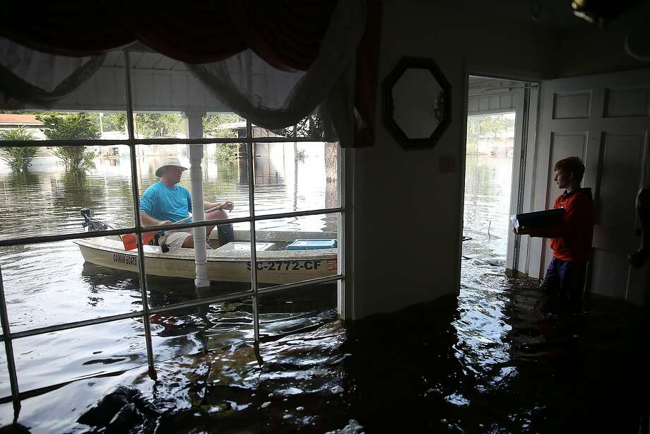 Allen Poston (left) and his nephew, Braxton Blakley, check on the condition of a relative's home that was inundated after dams breached upstream of the town of Andrews, S.C. Photo: Joe Raedle, Getty Images