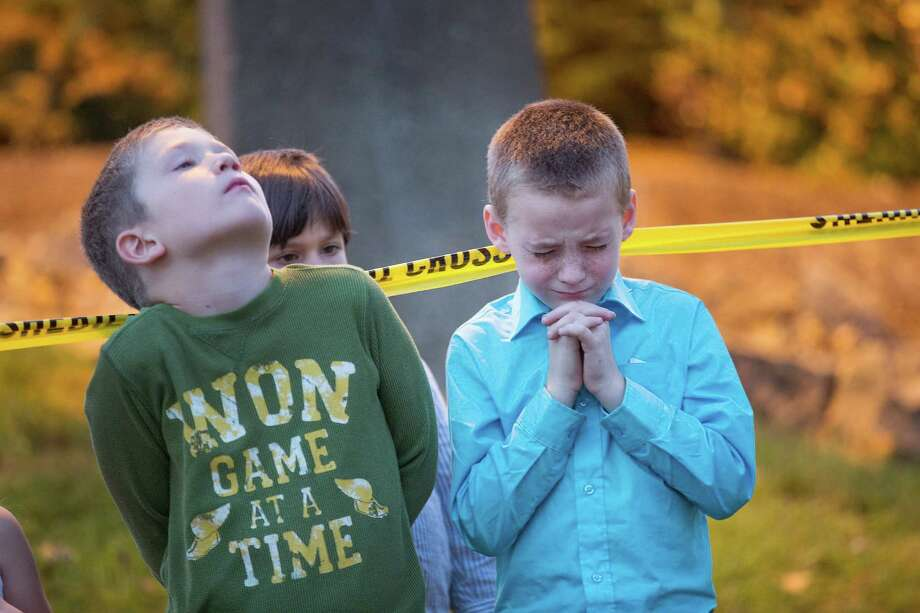 Young church members  pray at a memorial on the campus of Umpqua Community College, where 10 people, including the shooter, were killed in a shooting spree. A reader calls for stricter background checks for gun purchases. Photo: Scott Olson /Getty Images / 2015 Getty Images