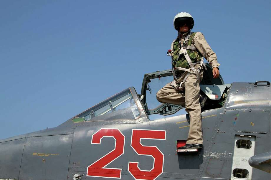 A Russian pilot poses at a cockpit of SU-25M jet fighter at Hmeimim airbase in Syria. Vladimir Putin's gambits in Syria, Crimea and Ukraine might be more about blunting NATO and U.S. power and influence than anything else. Photo: Alexander Kots /Associated Press / www.kp.ru