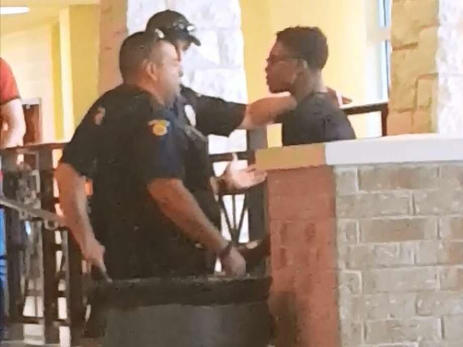 A video circulating on social media shows a Round Rock police officer grabbing a high school student's neck before throwing him to the ground on Thursday. Photo: Courtesy