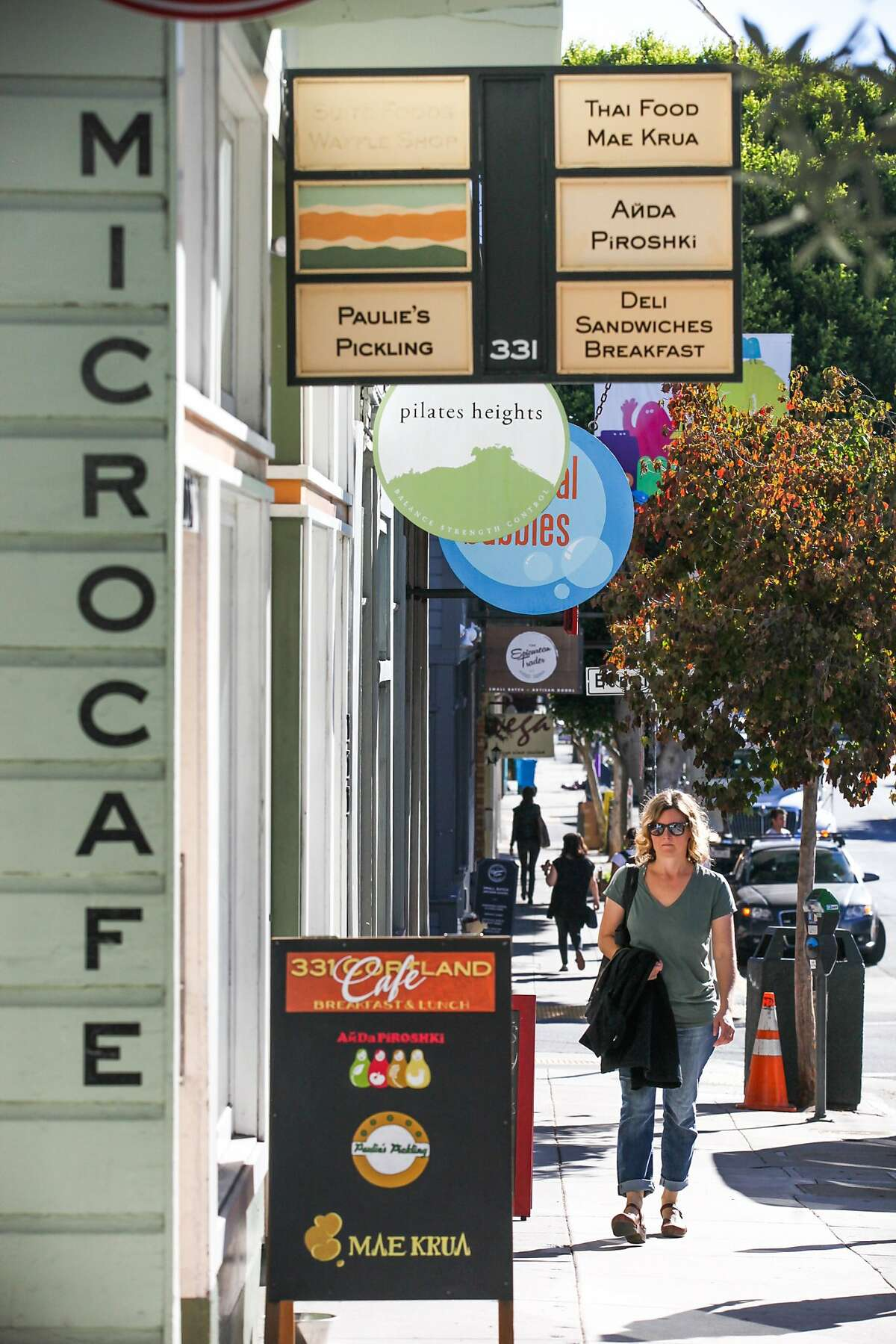 Caroline Griswold who has lived in Bernal Heights for a decade walks by new stores in Bernal Heights, San Francisco, California on October 9, 2015. She has seen the neighborhood transform and says,