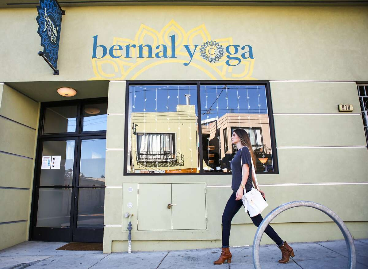 Allie Whitbord, who lives in Bernal Heights, walks past the local yoga studio in San Francisco, California on October 9, 2015. In 2010 only about 7 percent of Bernal Heights houses were over $1 million and now it is over 80%.