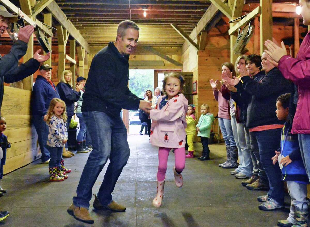 Colby Matthews dances a Virginia Reel with daughter Lily, 4, during a Kids Care Preschool field trip to Wunsapana Farm Friday Oct. 9, 2015 in Altamont, NY. (John Carl D'Annibale / Times Union)