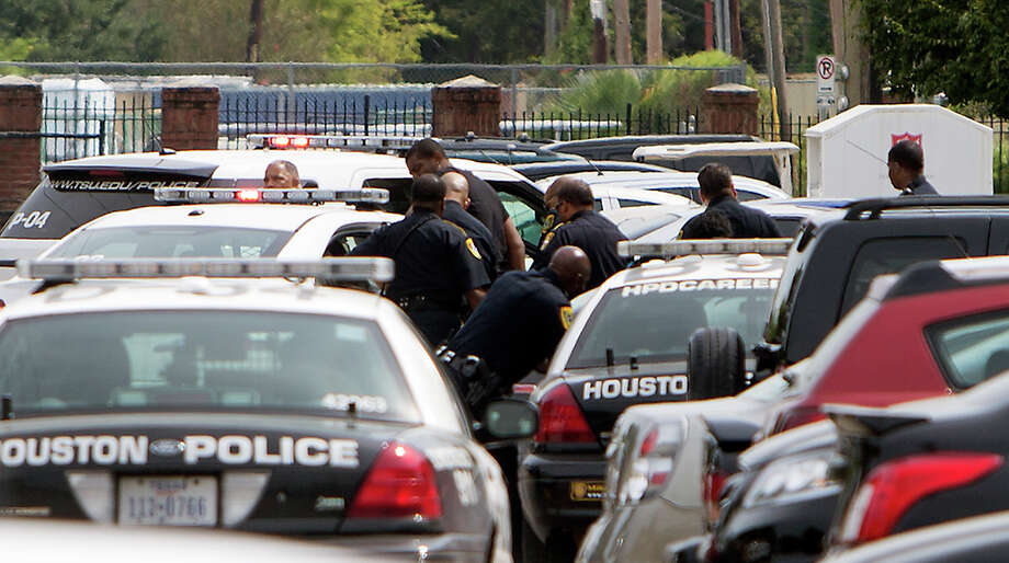 Authorities search for a man as they investigate Friday's shooting. A student was killed and another person was wounded in a shooting outside a student-housing complex on Friday, and police have detained at least two people, authorities said. Photo: Cody Duty, Associated Press / Houston Chronicle