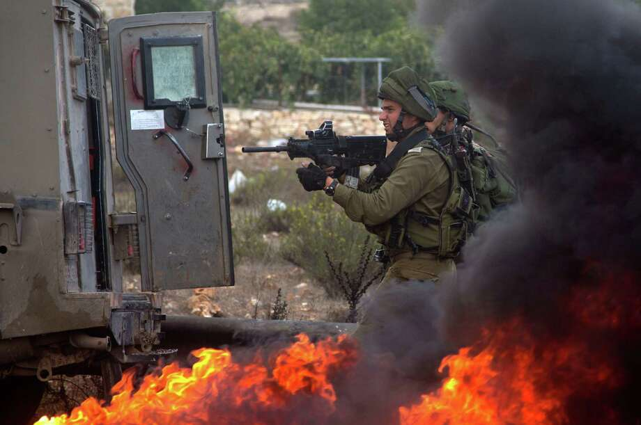 Israeli troops take aim during clashes Friday with Palestinians, near Ramallah on the West Bank. Violence  also has spread to Gaza. Photo: Majdi Mohammed, STR / AP