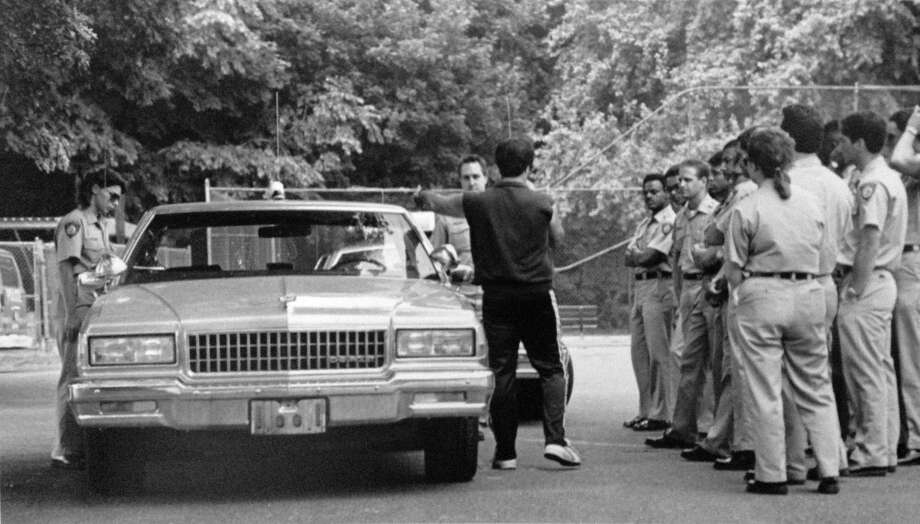 Edmond Melfi of the Stamford Police Department teaches new recruits the proper way to approach a stopped car in June 1988. The cadets pictured are two months into their 29 week training period. Photo: John Voorhees / John Voorhees / Stamford Advocate Contributed