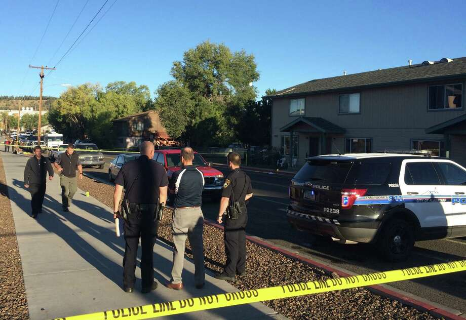 Authorities gather outside a student dormitory in Flagstaff, Ariz., Friday, Oct. 9, 2015, after an early morning fight between two groups of college students escalated into gunfire leaving one person dead and three others wounded, authorities said. The shooting occurred near the Northern Arizona University campus. (AP Photo/Felicia Fonseca) Photo: Felicia Fonseca, STF / AP
