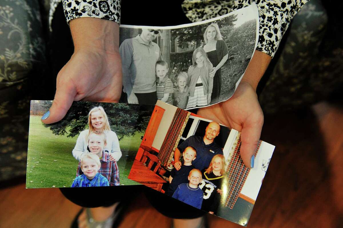 Alison, a recovering drug user, holds photographs of her husband and their three children during an interview at The Next Step program on Tuesday, Sept. 29, 2015, in Albany, N.Y. (Paul Buckowski / Times Union)