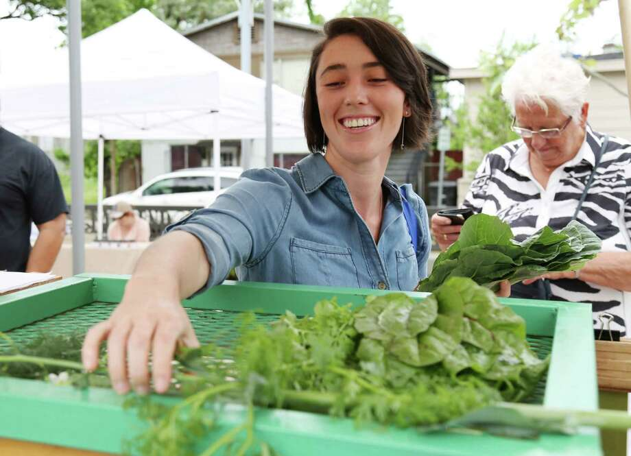 Caitlin McNeely buys fresh collard greens and other vegetables from Sown & Grown Urban Farm at the inaugural East End Farmer's Market on the Navigation Blvd Esplanade Sunday, April 12, 2015, in Houston. ( Jon Shapley / Houston Chronicle ) Photo: Jon Shapley, Staff / © 2015 Houston Chronicle