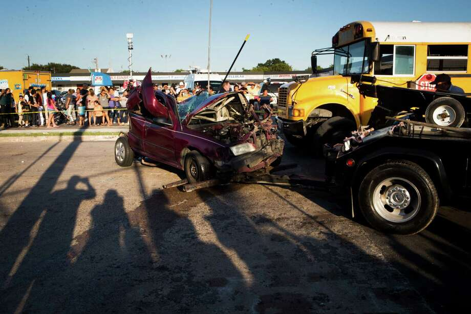 A car sits mangled after an SUV hit from behind, causing the vehicle to crash into a school bus on Rampart near Bissonnet on Monday afternoon. The driver and her two young children survived the crash but were taken to an area hospital. Some children on the bus also were injured. ( Marie D. De Jesus / Houston Chronicle ) Photo: Marie D. De Jesus, Staff / © 2015 Houston Chronicle