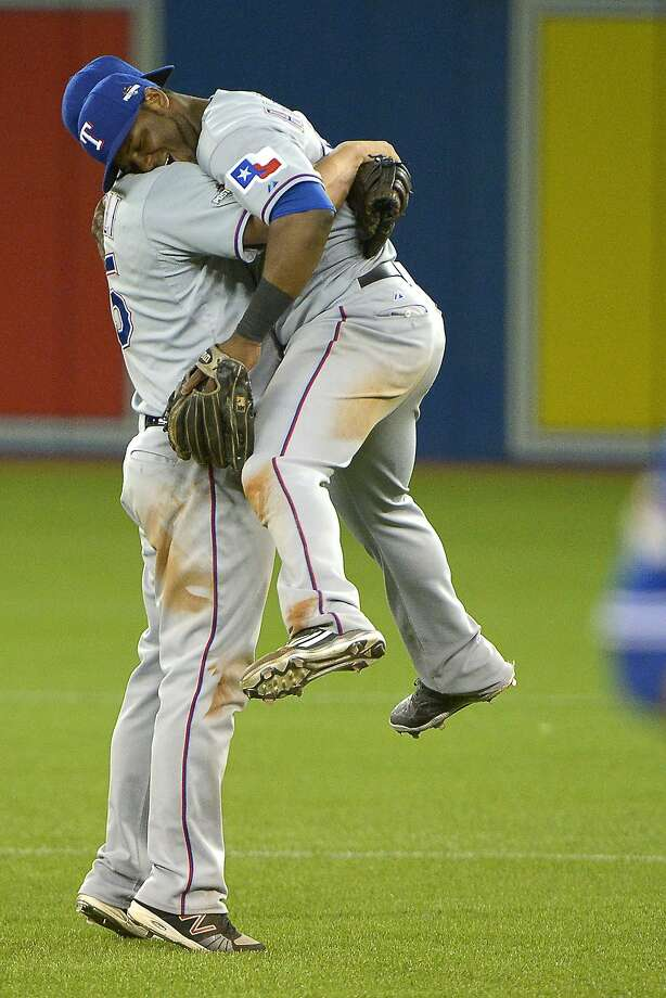 Texas' Mike Napoli picks up Hanser Alberto, author of the game-winning hit that gave the Rangers a 2-0 series lead. Photo: Max Faulkner, McClatchy-Tribune News Service