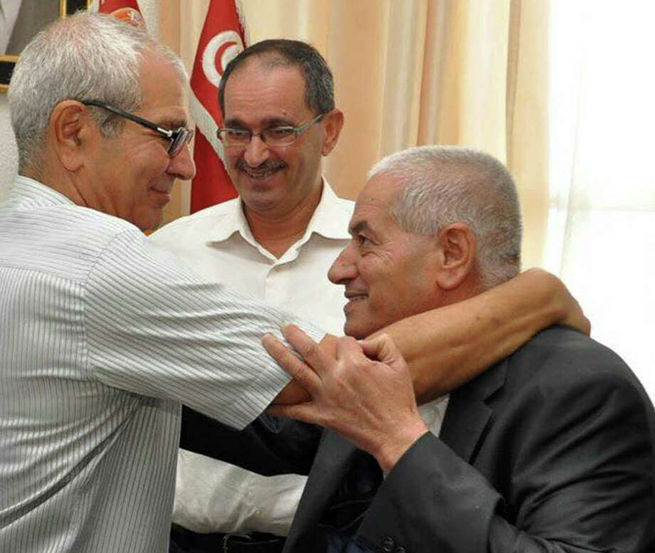 Houcine Abassi, secretary general of the Tunisian General Labour Union (UGTT), right, is congratulated by unidentified union members in his office at the headquarters in Tunis, Tunisia, Friday, Oct. 9, 2015. Abassi is one of the four members of the Tunisian National Dialogue Quartet to be awarded the 2015 Nobel Peace Prize on Friday by the Norwegian Nobel Committee. (AP Photo) Photo: STR / AP