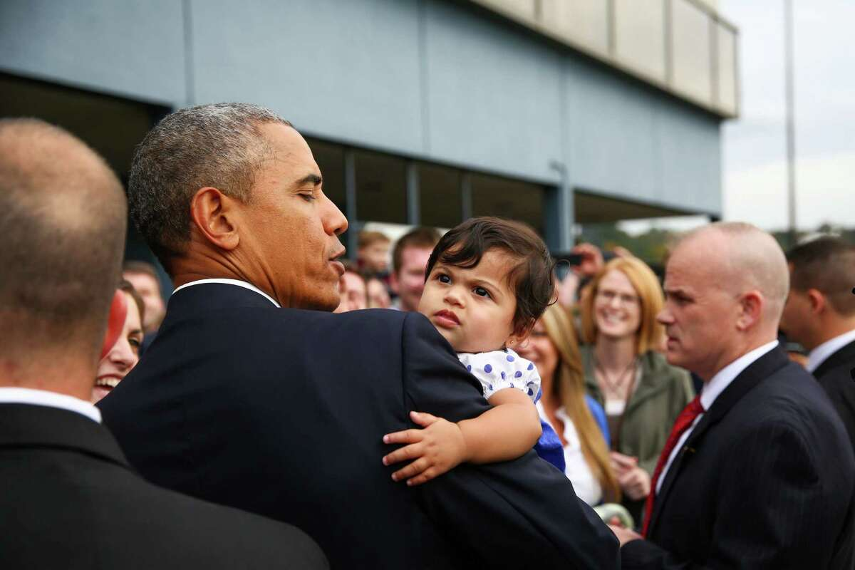 President Barack Obama holds six month-old Stella Hakam at Boeing Field during a brief visit to Seattle on Friday, Oct. 9, 2015. The president stopped in the Seattle area for a fundraiser and event to support Sen. Patty Murray, D-Wash. Obama came to Seattle after a stop in Roseburg, Oregon, where he visited a week after a school shooting there.