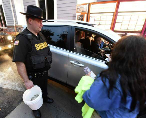 Saratoga County Sheriff's Deputy Steve Willetts and Peg Adams of the Special Olympics collect donations from customers to support Special Olympics at the Dunkin Donuts early Friday morning Oct. 9, 2015 in Malta, N.Y.       (Skip Dickstein/Times Union) Photo: SKIP DICKSTEIN / 10033643A
