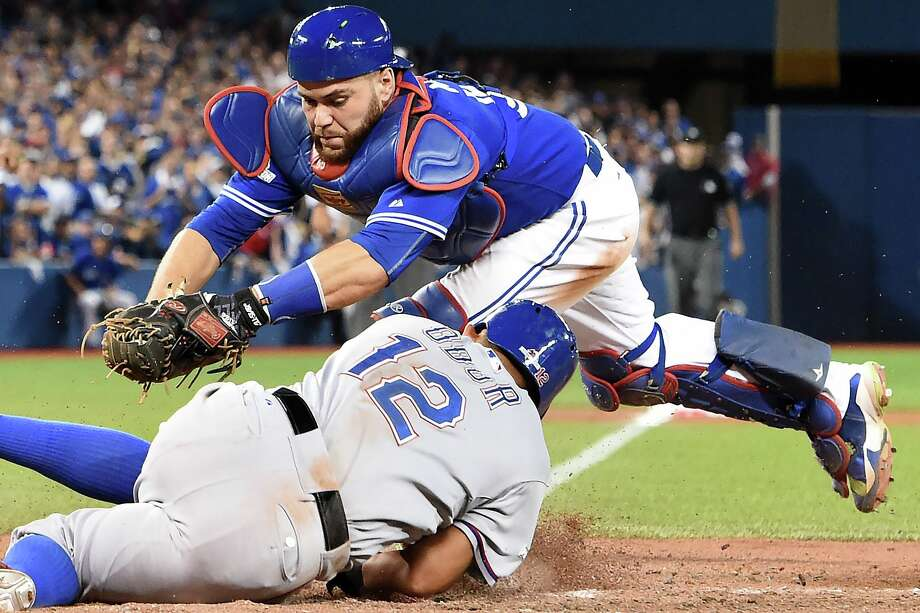 Blue Jays catcher Russell Martin, top, fails to tag out the Rangers' Rougned Odor in the 14th inning. Photo: Frank Gunn, SUB / The Canadian Press