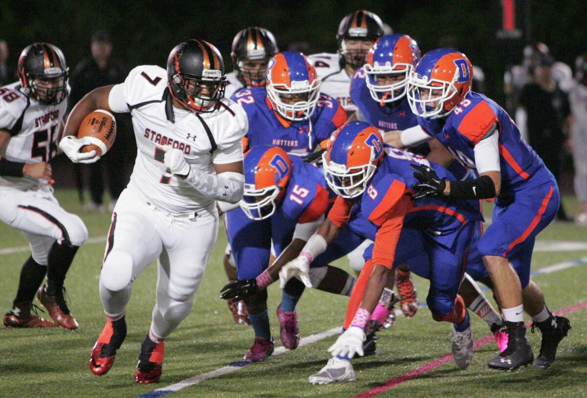 Stamford's Tyrel Diaz (7) carries the ball under chase by Danbury defenders during the first half of a varsity football game in Danbury on Oct. 9, 2015.