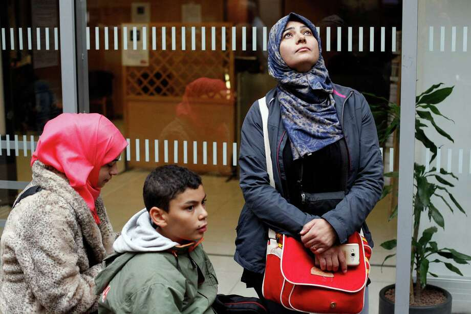 In this Thursday Sept. 24, 2015 photo, Syrian refugees Amena Abomosa, 43, right, her children Isra, 18, left, and Muhammad, 12, wait prior to boarding a train to Vannes, western France, in the Montparnasse railway station, in Paris. Her slain husband, bombed-out Damascus home and refugee life are behind her. The recipient of a coveted asylum-seeker visa, Syrian teacher Amena Abomosa is settling into a new life in France with her family. But now what? They are among the few amid a sea of desperate Syrians to arrive in Europe with prior approval to seek haven. British Prime Minister David Cameron and other European leaders would prefer for all refugees to come this way – applying at European embassies abroad, undergoing careful screening and entering the EU legally. Everyone else, they argue, should stay away, instead of risking perilous journeys. (AP Photo/Thibault Camus) Photo: Thibault Camus / Associated Press / AP